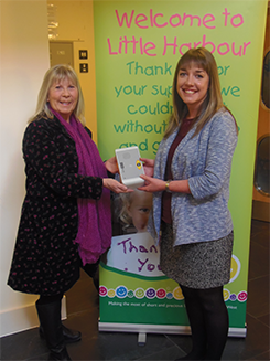 Caroline Swain accepts a RoomMate from ADi's, Helen Kemp on behalf of Children's Hospice South West