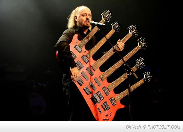 Bill Bailey playing his 6 neck guitar to an audience