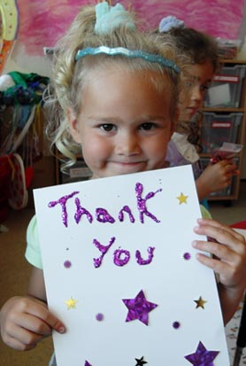 Little girl holding a sign saying thankyou